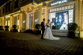 Hanoi, Vietnam, bride and groom having their picture taken at night by Hotel Metropole, a custom for women about to get married - David Bacon - 2010s,2016,adult,adults,Asia,asian,asians,bride,brides,couple,COUPLES,culture,custom,dress,FEMALE,Getting Married,Hanoi,Hotel,Hotel Metropole,HOTELS,husband,husbands,LFL,LIFE,Lifestyle,lights,marriage
