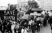 Supporters of Biafra protest against the British Government supplying arms to Nigeria during the Nigerian Civil War, London, 1968. Simon Guttmann, newspapers under his arm. - Romano Cagnoni - 1960s,1968,activist,activists,against,BAME,BAMEs,banner,banners,Biafra,Biafran,black,BME,bmes,CAMPAIGN,campaigner,campaigners,CAMPAIGNING,CAMPAIGNS,Civil War,DEMONSTRATING,demonstration,DEMONSTRATIONS