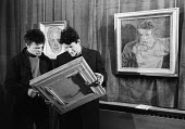 Artist Lucian Freud discussing one of his paintings with one of his favourite life models, Charlie Lumley at an exhibition of Freud's work, London, 1958. To their right is a painting titled Charles Lu... - Alan Vines - 1950s,1958,ACE,art,Art Gallery,artist,artists,arts,artwork,artworks,Charles Lumley,Charlie Lumley,cities,city,communicating,communication,conversation,conversations,culture,dialogue,discourse,discuss,