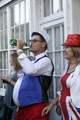 Queen Elizabeth II 90th birthday celebration weekend, drinkers at a street party Alcester Warwickshire - John Harris - 2010s,2016,2nd,90th,alcohol,birthday,BIRTHDAYS,bottle,bottles,CELEBRATE,CELEBRATING,celebration,CELEBRATIONS,communities,community,costume,costumes,dressed up,dressing up,drink,drinker,drinkers,drinki