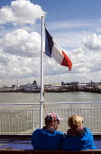 Couple on a ferry as it leaves the port of Calais, France, heading across the English Channel to Dover in the UK. - Stefano Cagnoni - EBF,2010s,2016,adult,adults,boat,boats,Calais,cap,channel port,COAST,Couple,COUPLES,Cross Channel Ferry,EBF,Economic,Economy,eu,europe,european,europeans,ferries,ferry,flag,flagpole,flags,France,frenc
