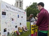 Jo Cox murder. Convoy to Calais supporters looking at flowers and messages left for murdered Labour MP Jo Cox, Parliament Square, London - Stefano Cagnoni - 2010s,2016,activist,activists,aid,assistance,CAMPAIGN,campaigner,campaigners,CAMPAIGNING,CAMPAIGNS,convoy,Convoy to Calais,death,deaths,DEMONSTRATING,demonstration,DEMONSTRATIONS,Diaspora,died,displac
