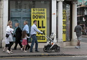 Family walking past dilapidated frontage of Austin Reed store closing down everything must go, including 1000 jobs, Stratford upon Avon - John Harris - 11-06-2016