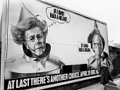 General Election Campaign 1983. Woman glances up at a billboard poster advertising an SDP Party Political Broadcast. Depicting Margaret Thatcher as The Tin Man and Michael Foot as The Scarecrow, chara... - Stefano Cagnoni - 1980s,1983,advert,ADVERTISED,advertisement,advertisements,advertising,ADVERTISMENT,billboard,billboards,brain,campaign,campaigning,CAMPAIGNS,CONSERVATIVE,conservative party,conservatives,democracy,ele