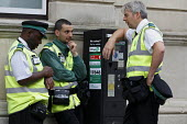 Civil Enforcement officers take a break by aparking ticket machine - John Harris - 2010s,2016,attendants,BAME,BAMEs,black,BME,bmes,break,break time,breaktime,CEO,Civil Enforcement Officer,CLJ,communicating,communication,conversation,conversations,Council Services,Council Services,di