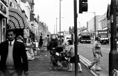 Streets of Handsworth, Birmingham, 1977 - Dave Evans - 1970s,1977,adult,adults,asian,Asians,babies,baby,BAME,BAMEs,Birmingham,black,BME,bmes,bought,buy,buyer,buyers,buying,child,CHILDHOOD,CHILDREN,cities,City,commodities,commodity,consumer,consumers,custo