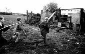Boys playing a game of war or Cowboys and Indians in a field on the outskirts of Reading, 1970 - Mary Elgin - 15-03-1970