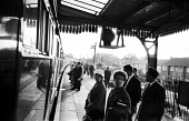 Early morning commuters waiting to board the train for London, Herne Bay Station, summer, 1965 - Patrick Eagar - 1960s,1965,adult,adults,arrival,arrivals,arrive,arrived,arrives,arriving,British Rail,carriage,carriages,cities,city,COMMUTE,commuter,commuters,commuting,EBF,Economic,Economy,FEMALE,from work,journey,