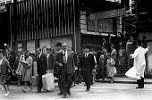 Early morning commuters making thier way to offices from Cannon Street Station, summer, 1965 and being directed across the road by a white coated City of London police officer - Patrick Eagar - 1960s,1965,adult,adults,arrival,arrivals,arrive,arrived,arrives,arriving,British Rail,businessman,businessmen,cities,City,City of London,CLJ,COMMUTE,commuter,commuters,commuting,crowd,crowded,disembar