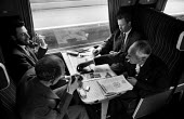 Early morning commuters playing dominoes whilst smoking their pipes on board the train from Kent to London, summer, 1965 - Patrick Eagar - 1960s,1965,adult,adults,British Rail,businessman,businessmen,carriage,carriages,CIGARETTE,cigarettes,cities,city,COMMUTE,commuter,commuters,commuting,domino,dominoes,EBF,Economic,Economy,from work,gam