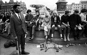 Demonstration against the Vietnam War, Trafalgar Square, London, 1967. Young people sit around the fountains, their casual style of dress contrasting greatly with the well dressed young black man, hol... - Patrick Eagar - 02-07-1967