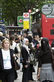 Commuters queuing for bus service due to the closure of London Underground by a strike. Listening to an Ipod. - Duncan Phillips - 10-06-2009