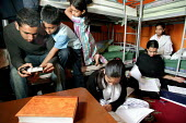 Overcrowding, tower Hamlets. Children try to do their homework in a cramped bedroom. Bengali family, Sanur Ali with wife Salima Begum and their five children living with two other relatives in a damp... - Jess Hurd - 02-10-2004