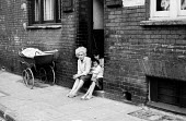 Women with a young child sitting on the doorstep of their home in a poor part of London, early 1960s - Romano Cagnoni - 11-07-1962