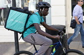 Deliveroo riders delivering takeaway food by bicycle Leamington Spa, Warwickshire - John Harris - self employed,2010s,2016,away,backpack,BAME,BAMEs,BEMM,bicycle,bicycles,BICYCLING,Bicyclist,Bicyclists,BIKE,BIKES,Black,BME,bmes,by hand,carries,carry,carrying,collecting,contracts,Courier,Couriers,cy