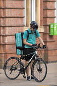 Deliveroo riders delivering takeaway food by bicycle Leamington Spa, Warwickshire - John Harris - 2010s,2016,app,application,applications,apps,away,backpack,bicycle,bicycles,BICYCLING,Bicyclist,Bicyclists,BIKE,BIKES,by hand,carries,carry,carrying,CELLULAR,collecting,communicating,communication,con