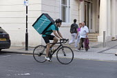 Deliveroo riders delivering takeaway food by bicycle Leamington Spa, Warwickshire - John Harris - self employed,2010s,2016,away,backpack,bicycle,bicycles,BICYCLING,Bicyclist,Bicyclists,BIKE,BIKES,by hand,carries,carry,carrying,collecting,contracts,Courier,Couriers,cycle,cycles,cycling,Cyclist,Cycl