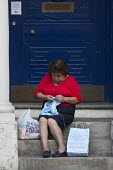 Grandmother sitting on steps knitting childrens clothing, Leamington Spa, Warwickshire - John Harris - 30-07-2016