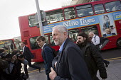 Jeremy Corbyn with a Nine Lives film advertisement after joining an Action For Rail protest against rail fare rises and for public ownership, London Bridge Station, London. - Jess Hurd - 2010s,2016,Action For Rail,activist,activists,advertisement,advertisements,advertising,against,ASLEF,banner,banners,Bridge,bus,bus service,buses,campaign,campaigner,campaigners,campaigning,CAMPAIGNS,D