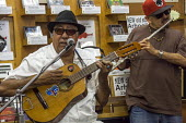 "El Cerrito, California, Cuban musician Heriberto ""Tito"" Gonzalez, composer and band leader playing a tres with Ruben Hurtado, flautist and an impromptu group of Son cubano musicians, Down Home Music S... - David Bacon - 2010s,2016,ACE,Arts,BAME,BAMEs,band,bands,BEMM,BEMMs,BME,bmes,California,cities,City,composer,Cuba,cuban,cubans,Culture,diversity,ethnic,ethnicity,flute,guitar,guitars,Home,leader,male,man,melody,men,"