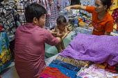 Battambang, Cambodia, stall holders give their baby a bath at the back of the shop - David Bacon - 24-12-2015