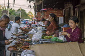 Battambang, Cambodia, stall in the Phsar Nath Market where selling food at a street stall - David Bacon - 2010s,2015,Asia,asian,asians,Battambang,bought,buy,buyer,buyers,buying,cafe,cafes,Cambodia,cambodian,cambodians,catering,chairs,cities,City,commodities,commodity,consumer,consumers,COOKERY,cooking,cur