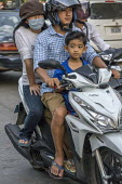 Battambang, Cambodia, family riding a scooter through the traffic - David Bacon - 24-12-2015
