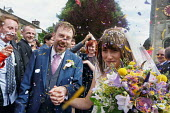 Hannah Edwards and Kieran Durkan getting married, being showered with confetti as they leave the church, Yorkshire - John Harris - 2010s,2016,bouquet of flowers,bride,brides,Bunch of Flowers,church,churches,confetti,dress,EMOTION,EMOTIONS,families,family,FEMALE,getting married,groom,happiness,happy,HUMOUR,husband,husbands,laugh,l