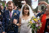 Hannah Edwards and Kieran Durkan getting married, being showered with confetti as they leave the church, Yorkshire - John Harris - 2010s,2016,bouquet of flowers,bride,brides,Bunch of Flowers,church,churches,confetti,dress,EMOTION,EMOTIONS,families,family,FEMALE,getting married,groom,happiness,happy,husband,husbands,leave,Leisure,