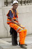 Recording in progress. Construction worker with Edesix video badge having a break in the summer heat, Knightsbridge, London. VB-100 body worn video camera system is styled as an ID card holder worn ar... - Jess Hurd - 2010s,2016,bodies,body,break,break time,breaktime,builder,builders,BUILDING,building worker,camera,cameras,cities,city,Construction,Construction Industry,Edesix,employee,employees,Employment,hard hat,