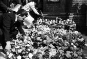 Mourners laying flowers at the funeral of Kelso Cochrane, St Michael and All Angels Church, Ladbroke Grove, West London, 1959. Kelso Cochrane, an Antiguan immigrant, was stabbed by 3 white youths, tho... - Alan Vines - 1950s,1959,Angels,Anti Fascist,Anti Racism,anti racist,BAME,BAMEs,bigotry,black,Black History,BME,bmes,bouquet,bouquet of flowers,Bunch of Flowers,Church,churches,cities,city,CLJ,crime,DEATH,DEATHS,Di