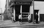 Street corner, Stiles Brothers Bakery near Chapel Market, Islington, London, 1976 - John Sturrock - 1970s,1976,baker,bakers,bakery,bellbottoms,bought,bread,Brothers,buying,Chapel,cities,City,commodities,commodity,consumer,consumers,corner shop,customer,customers,EBF,Economic,Economy,FEMALE,Islington