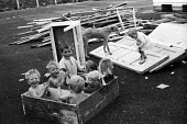 Children from travellers families playing together among discarded furniture on their site on the outskirts of London, 1969. - Thurston Hopkins - ,1960s,1969,animal,animals,BAME,BAMEs,BME,bmes,box,boxes,boy,boys,canine,child,CHILDHOOD,children,cities,city,communities,community,discarded,dispose,diversity,dog,dogs,EMOTION,EMOTIONAL,EMOTIONS,ethn