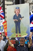 Artist Kaya Mar painting of Theresa May as a police woman. March for Europe against the Brexit EU referendum result, Central London. - Jess Hurd - 2010s,2016,ACE,activist,activists,adult,adults,against,art,Artist,artists,arts,artwork,artworks,Brexit,campaign,campaigner,campaigners,campaigning,CAMPAIGNS,culture,democracy,DEMONSTRATING,demonstrati