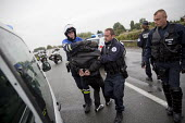 Police arrest protester against blockade of truckers and farmers demanding Calais Jungle refugee camp closure joined by Port of Calais dockers. France. - Jess Hurd - 2010s,2016,activist,activists,adult,adults,against,anti,arrest,arrested,arresting,AUTO,AUTOMOBILE,AUTOMOBILES,AUTOMOTIVE,bike,bikes,block,blockade,BLOCKADING,blocked,blocking,blocks,Calais,camp,CAMPAI