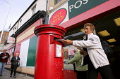 A woman posts a letter into a traditional red postbox outside a Post Office, North Shields - Mark Pinder - 1990s,1999,box,boxes,communicating,communication,customer,customers,EBF Economy,FEMALE,letter,Letter box,Letter boxes,Letterbox,Letterboxes,letters,mail,office,outside,people,person,persons,pillar,pos
