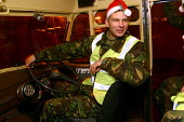 Soldiers manning a green goddess attending a minor fire at an industrial site in North Shields, Tyne and Wear. Wearing christmas santa hats in the green goddess given by a local resident who brought t... - Mark Pinder - 24-11-2002