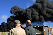 Residents watching smoke from an industrial fire at the Distillex chemical recycling plant, North Shields. Residents and workers within a half mile downwind of the accident were evacuated. The plume... - Mark Pinder - 12-04-2002