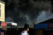 Policeman watching an industrial fire at the Distillex chemical plant, North Shields. 12/4 2002 Residents and workers within a half mile downwind of the accident were evacuated. The plume could be se... - Mark Pinder - 12-04-2002