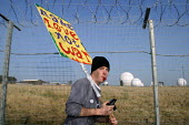 A protestor with a Make Love Not War placard beside the perimeter fence at the Foil the Base event. Menwith Hill listening base, North Yorkshire. 22/3 2003. - Mark Pinder - 22-03-2003