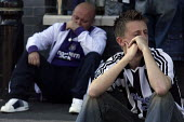 A dejected looking Newcastle United Football Club supporter with Northern Rock shirt, outside the club's Saint James Park ground having just seen his club relegated from the Premier League in a 1-0 aw... - Mark Pinder - 24-05-2009