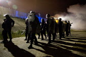 Police fire tear gas into the Jungle refugee camp, Calais, France. - Jess Hurd - 2010s,2016,adult,adults,armed,attack,attacking,attacks,BAME,BAMEs,BME,bmes,border,Calais,camp,camps,CLJ,crisis,CRS,cs gas,Diaspora,displaced,diversity,ethnic,ethnicity,eu,Europe,european,europeans,fir
