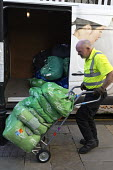 Worker unloading and delivering laundry to a hotel, Stratford-upon-Avon - John Harris - 2010s,2016,bag,bags,cart,carts,deliveries,DELIVERING,delivery,driver,drivers,DRIVING,EARNINGS,EBF,Economic,Economy,heavy weight,hospitality,hotel,HOTELS,Income,inequality,Johnsons Stalbridge Linen Ser