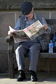 Elderly man sitting on a bench reading The Sun newspaper, Stratford-upon-Avon - John Harris - 2010s,2016,adult,adults,age,ageing population,bench,cognition,consumer,consumers,customer,customers,dominant narrative,elderly,foreign,foreigner,foreigners,from,immigrant,immigrants,journalism,learn,l