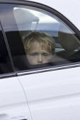 Small boy looking out of a car window. - John Harris - &,2010s,2016,AUTO,AUTOMOBILE,AUTOMOBILES,AUTOMOTIVE,bored,boredom,boring,boy,boys,car,cars,child,CHILDHOOD,children,daydream,daydreaming,disinterested,holiday,holiday maker,holiday makers,holidaymaker