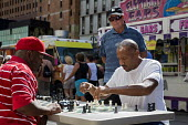 Detroit, Michigan, Men playing chess on the street during the Detroit Jazz Festival - Jim West - ,2010s,2016,African American,African Americans,BAME,BAMEs,black,BME,bmes,board,chess,cities,City,concentration,Detroit,Detroit Jazz Festival,diversity,ethnic,ethnicity,festival,FESTIVALS,focus,game,ga
