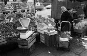 Pensioner looking at prices on a street market fruit and veg stall ,Tower Hamlets, one of the poorest boroughs in the UK, London 1976 - Angela Phillips - 1970s,1976,adult,adults,age,ageing population,apple,apples,bought,buy,buyer,buyers,buying,choice,choosing,cities,City,commodities,commodity,consumer,consumers,customer,customers,dates,deciding,decisio