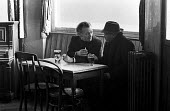 Two men drinking and talking in a run down pub at lunchtime, Tower Hamlets, one of the poorest boroughs in the UK, 1976 - Angela Phillips - 1970s,1976,alcohol,BAME,BAMEs,beer,BEMM,black,BME,bmes,BREAK,chat,chatting,cigarette,CIGARETTES,cities,City,communicating,communication,conversation,conversations,conversing,dialogue,DINNER,dinners,DI