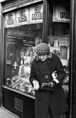 Pensioner checking her change outside a Cut Price shop in Tower Hamlets, one of the poorest boroughs in the UK, 1976. - Angela Phillips - 1970s,1976,adult,adults,age,ageing population,bought,buy,buyer,buyers,buying,cash,checking,cities,City,coins,commodities,commodity,consumer,consumers,count,counting,customer,customers,Cut Price,cut pr