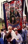 Durham Miners Gala, 1983. Miners and their families march on the 100th Anniversary of the Durham Miners Gala. The Chopwell Lodge Red banner, famously bearing the portraits of Karl Marx, Vladimir Lenin... - Stefano Cagnoni - 1980s,1983,ACE,anniversary,banner,banners,Big Meeting,boy,BOYS,carries,carry,carrying,centenary,child,CHILDHOOD,children,Chopwell Lodge,communism,Communist Party,communists,County Durham,Culture,Durha